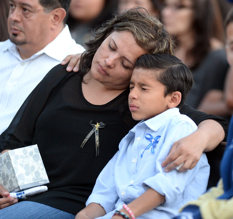 Description of . Veronica Soriano, mother of Adrian Castro, 19, holds her youngest son, Solan, 10, during a memorial gathering for him at El Monte High School Monday evening April 14, 2014. Castro was one of nine students killed in the bus crash in Orland, Calif. (Staff Photo by Keith Durflinger/San Gabriel Valley Tribune)