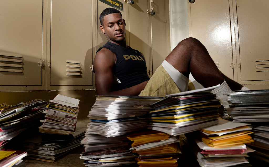 """. Long Beach Poly\'s John \""""JuJu\"""" Smith sits next to thousands of pieces of college football recruiting mail, he is one of the top ten recruit in the nation in Long Beach, CA. Tuesday December 24, 2013."""