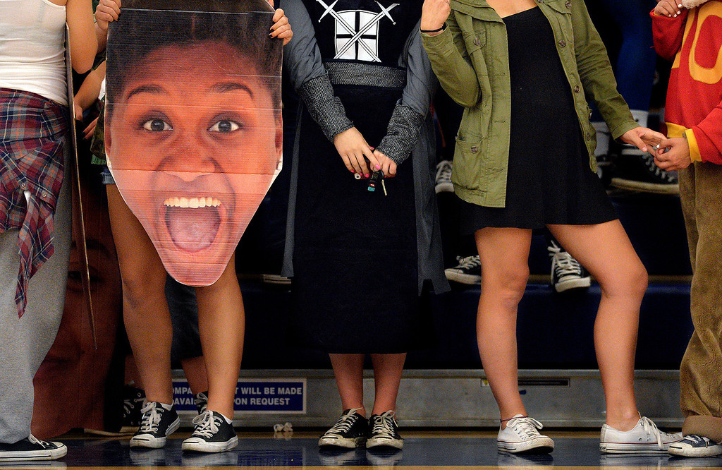 . Los Alamitos high school students holds big head photos of the schools volleyball team during a game against Newport Harbor during a rematch at Los Alamitos, Ca. Thursday October 31, 2013.