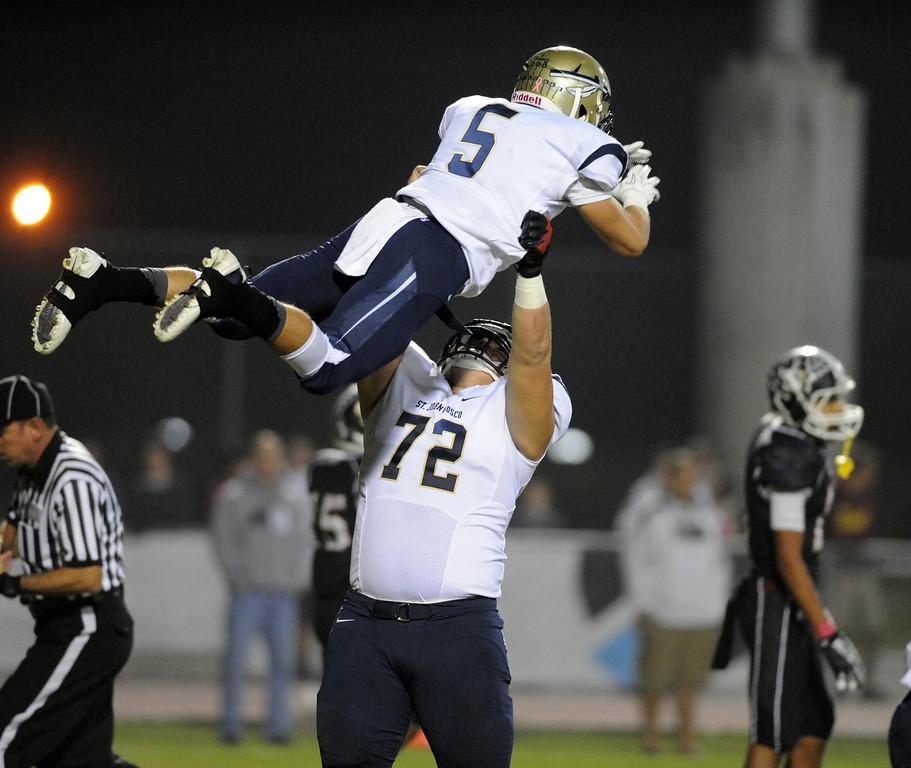 . St. John Bosco\'s Elijah Zabuldoff (72) picks up Sean McGrew (5) after McGrew\'s first quarter touchdown in the Trinity League high school football in Mission Viejo, CA. on Friday, October 25, 2013. (Photo by Sean Hiller/Press Telegram).