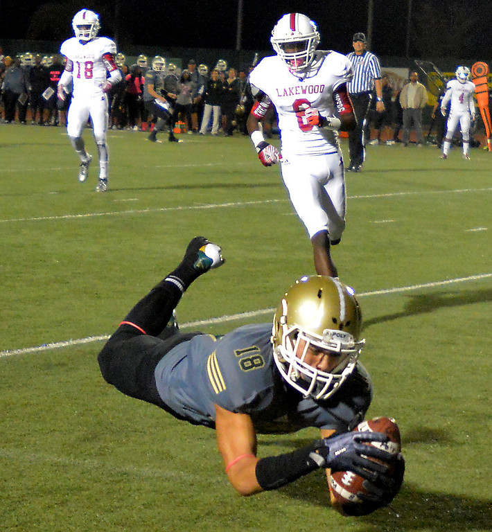 . Poly\'s Christian Pabico dives into the end zone for a touchdown over Lakewood\'s Tyler Dotts in Friday\'s Moore League high school football game at Veterans Stadium in Long Beach, CA. on October 18, 2013. (Photo by Sean Hiller/Press Telegram)