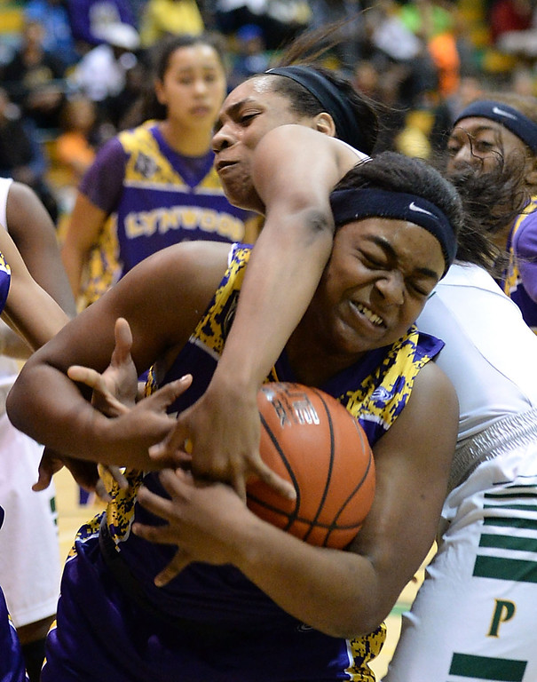 . Long Beach Poly\'s Jada Matthews (22) and Lynwood\'s Crystal Lomax (34) get tangled as they battle for a rebound in a nonleague girls basketball game Saturday, February 08, 2014, in Long Beach, CA.   Photo by Steve McCrank/Daily Breeze