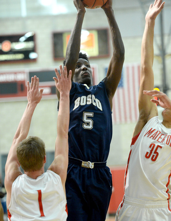 . St. John Bosco\'s Daniel Hamilton goes to the basket against Mater Dei\'s Rex Pflueger,left, and M.J. Cage in a Trinity League boy\'s basketball game at Mater Dei High School in Santa Ana, CA. on Wednesday, January 15, 2014. (Photo by Sean Hiller/ Daily Breeze).