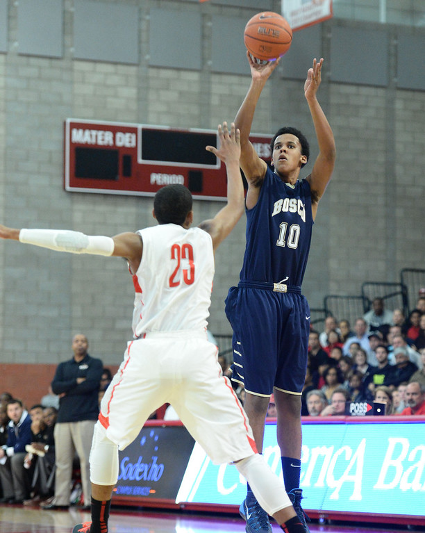 . St. John Bosco\'s Vance Jackson shoots a three point over Mater Dei\'s Isaiah Juarez in a Trinity League boy\'s basketball game at Mater Dei High School in Santa Ana, CA. on Wednesday, January 15, 2014. (Photo by Sean Hiller/ Daily Breeze).