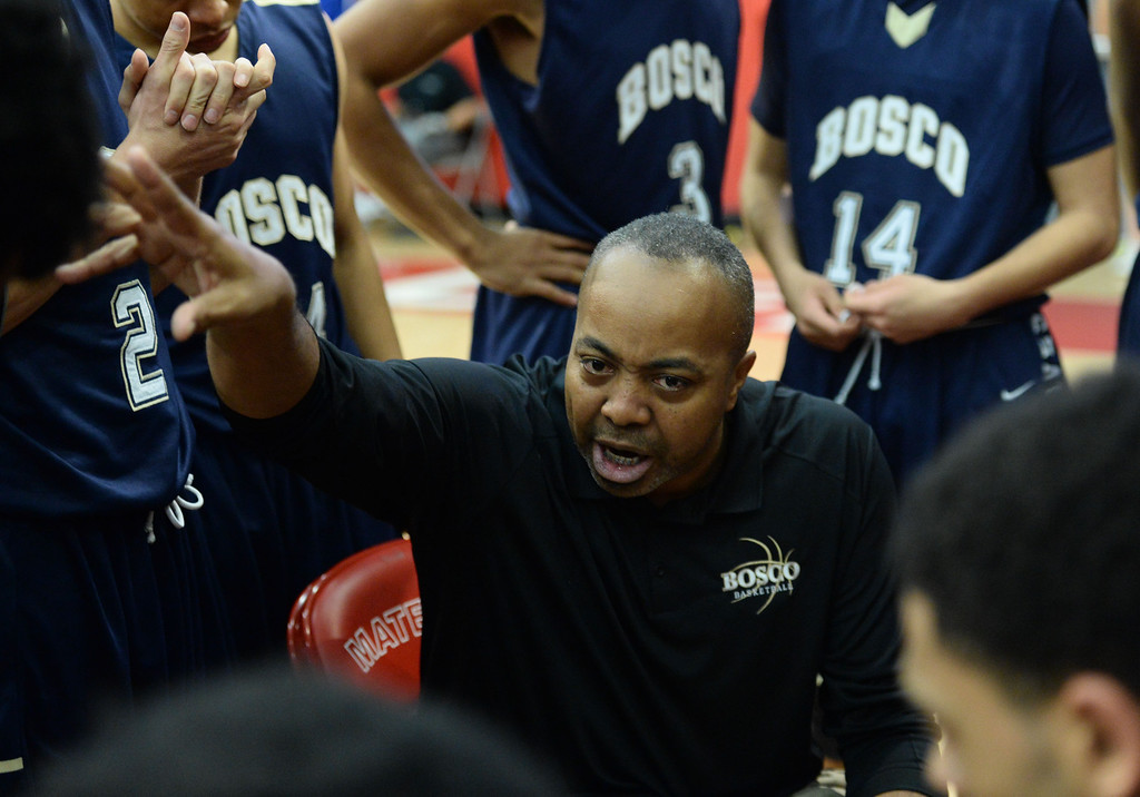 . St. John Bosco coach Derrick Taylor  huddles with his team as they battle Mater Dei in a Trinity League boy\'s basketball game at Mater Dei High School in Santa Ana, CA. on Wednesday, January 15, 2014. (Photo by Sean Hiller/ Daily Breeze).