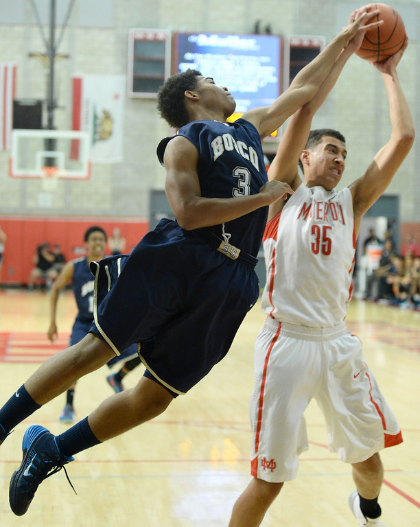 . St. John Bosco\'s Jared Harrell, left, battles Mater Dei\'s M.J. Cage in a Trinity League boy\'s basketball game at Mater Dei High School in Santa Ana, CA. on Wednesday, January 15, 2014. (Photo by Sean Hiller/ Daily Breeze).