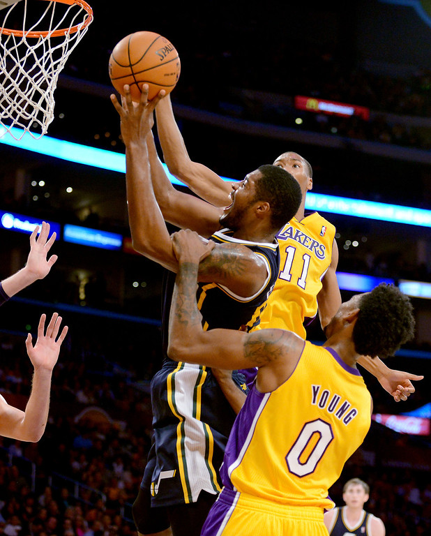 . Los Angeles Laker Wesley Johnson (11) guards Utah Jazz\'s Derrick Favors as Laker Nick Young (0) commits a foul first half in the NBA preseason basketball game at Staples Center in Los Angeles, CA. on Tuesday, October 22, 2013. (Photo by Sean Hiller/Daily News)