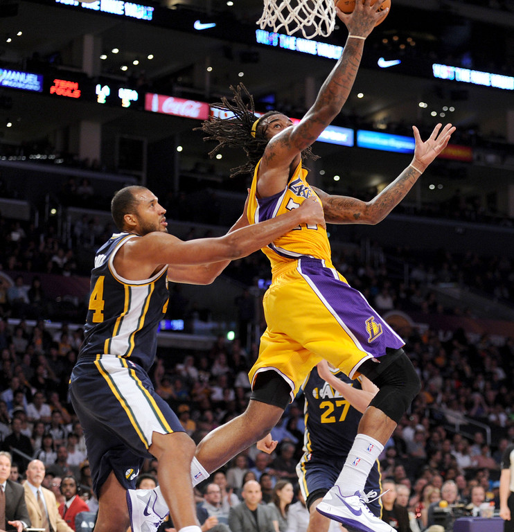 . Los Angeles LakerJordan Hill goes to the basket against the Utah Jazz\'s Brian Cook in the NBA preseason basketball game at Staples Center in Los Angeles, CA. on Tuesday, October 22, 2013. (Photo by Sean Hiller/Daily News)