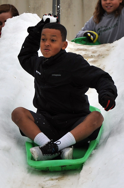 . Matthew Polk mutlitasks as he slides down the snow and throws a snowball at Bethany Lutheran School where 10 tons of snow was delivered Thursday to  thank students for a successful jog-a-thon.  Long Beach January 30, 2014. (Photo by Brittany Murray / Press Telegram)
