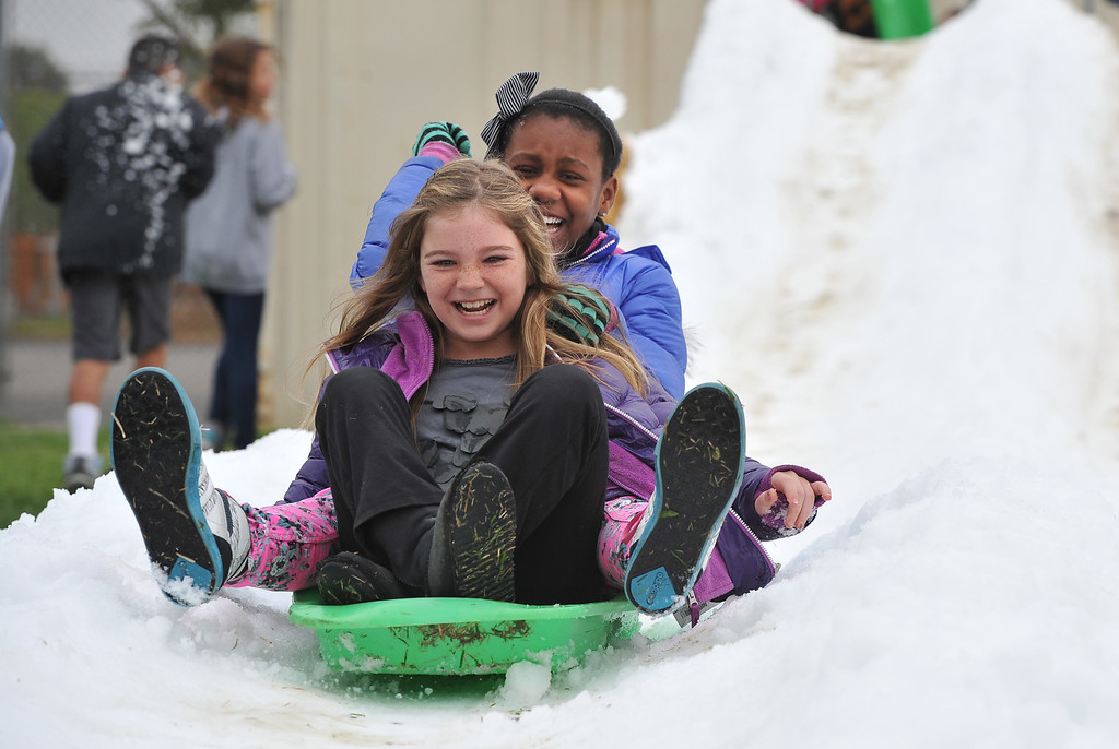 . Lana Caslan, front and Relei (CQ) Johnson slide down the snow at Bethany Lutheran School where 10 tons of snow was delivered Thursday to  thank students for a successful jog-a-thon.  Long Beach January 30, 2014. (Photo by Brittany Murray / Press Telegram)