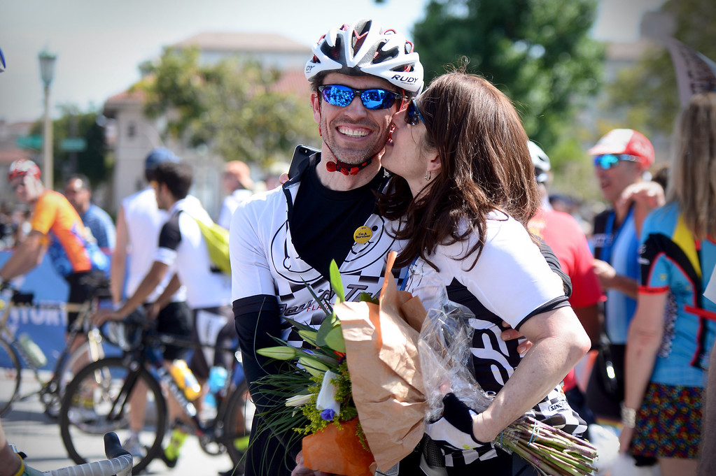 . Jill Harrison, of Flagstaff, Arizona, kisses her husband David Johns after stage 7 winner Peter Sagan threw his flowers to the crowd and Johns gave them to her during the Amgen Tour of California in Pasadena Saturday, May 17, 2014. Johns, a cancer survivor, is on the Amgen tour with friends from his college days and Harrison joined him for a tandem stage 7 ride. (Photo by Sarah Reingewirtz/Pasadena Star-News)