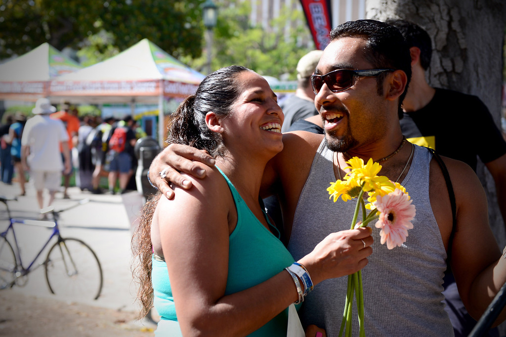 """. Jonathan Wolff, of Highland Park, gives his girlfriend Veronica RIvera flowers that Kind bars was handing out with their campaign \""""pick one and pass it on\"""" during the Amgen Tour of California in Pasadena Saturday, May 17, 2014. (Photo by Sarah Reingewirtz/Pasadena Star-News)"""