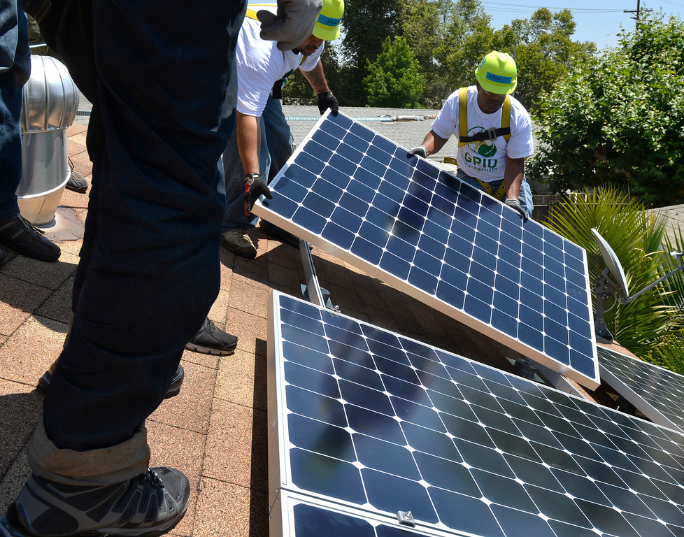 . Volunteers instal a free 2.8kW solar power system on a home in Long Beach, CA. Friday June 13, 2014. The system was installed by students from Los Angeles Trade Technical College�s Solar PV Technician certificate program. The college is partnering with GRID Alternatives, a non-profit group that provides job trainees with hands on experience and low-income families with lower energy bills. After installation, the energy system will supply between 75 and 90 percent of the homes energy needs. (Thomas R. Cordova-Daily Breeze/Press-Telegram)