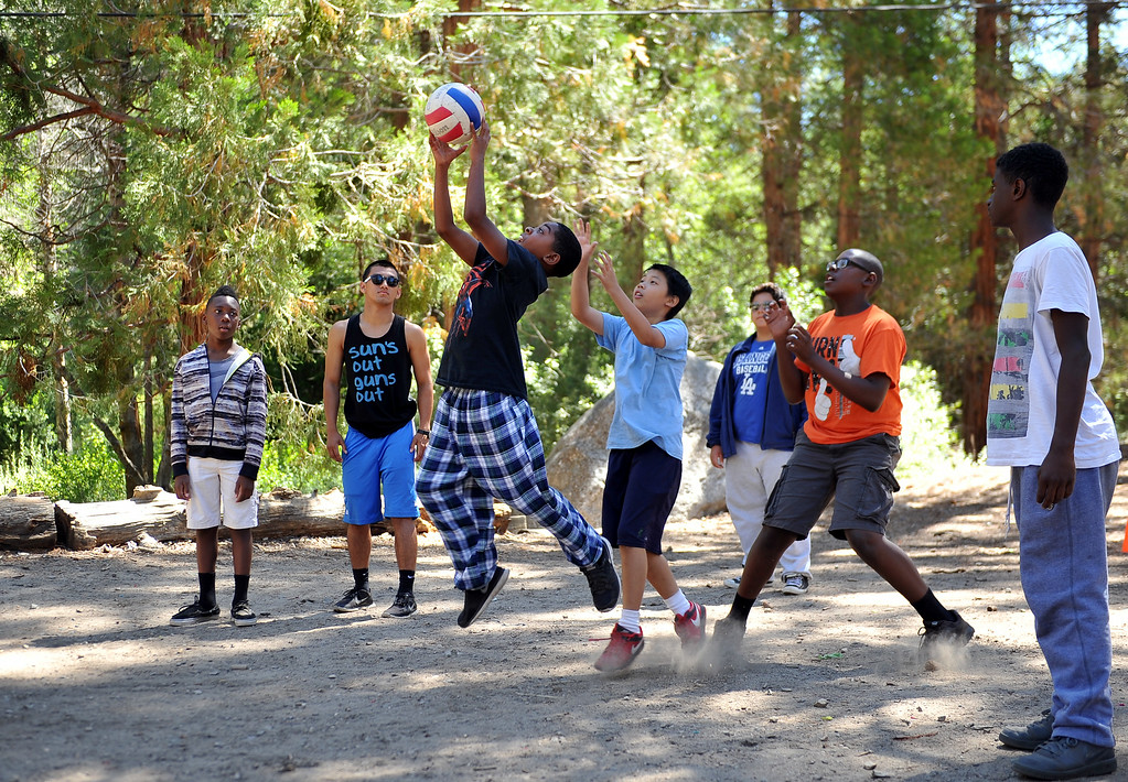 ". Young boys play a game of , ""prison ball,\"" at a volleyball net surrounded by tall oak, cedar and pine trees. The kids are enjoying the mountains for a week at Camp River Glen, a much different environment than their usual inner city home lives across Southern California. August 6, 2014. (Photo by Brittany Murray / Daily Breeze)"