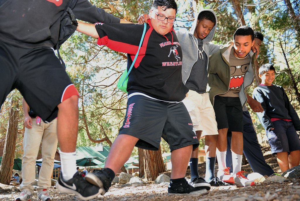 ". Young men participate in an exercise titled, ""crossing the great divide,\"" that required them to get the entire team from start to finish while touching feet and later with a balloon between each person. The kids are enjoying the mountains for a week at Camp River Glen, a much different environment than their usual inner city home lives across Southern California. August 6, 2014. (Photo by Brittany Murray / Daily Breeze)"