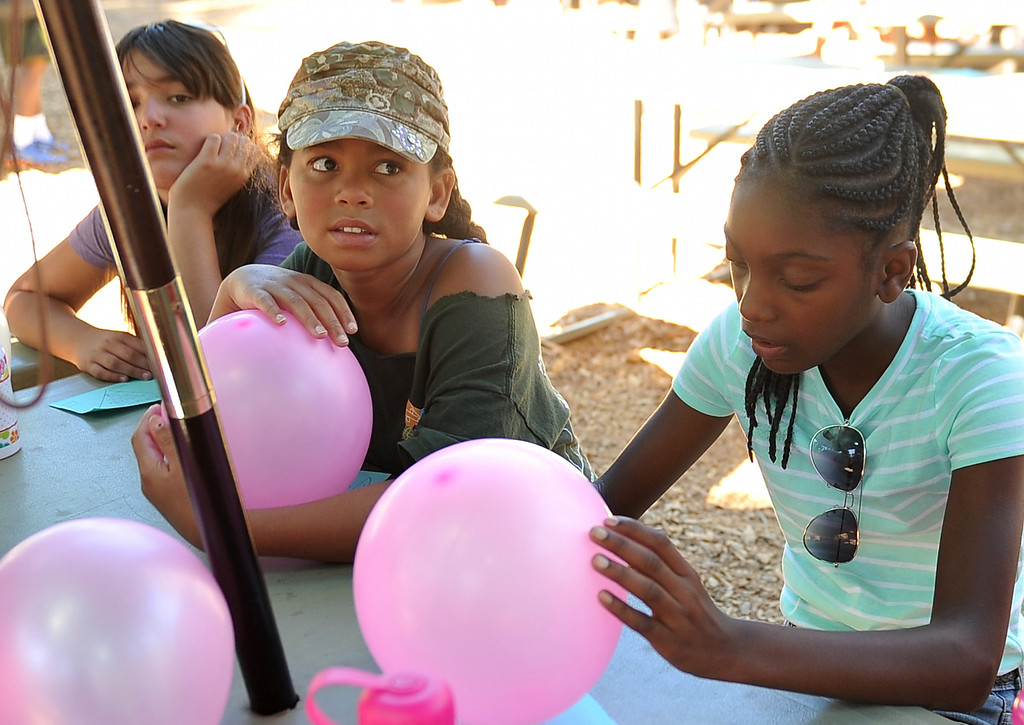 ". Young girls discuss what they learned from the exercise titled, ""crossing the great divide,\"" that required them to get the entire team from start to finish while touching feet and later with a balloon between each person. The kids are enjoying the mountains for a week at Camp River Glen, a much different environment than their usual inner city home lives across Southern California. August 6, 2014. (Photo by Brittany Murray / Daily Breeze)"