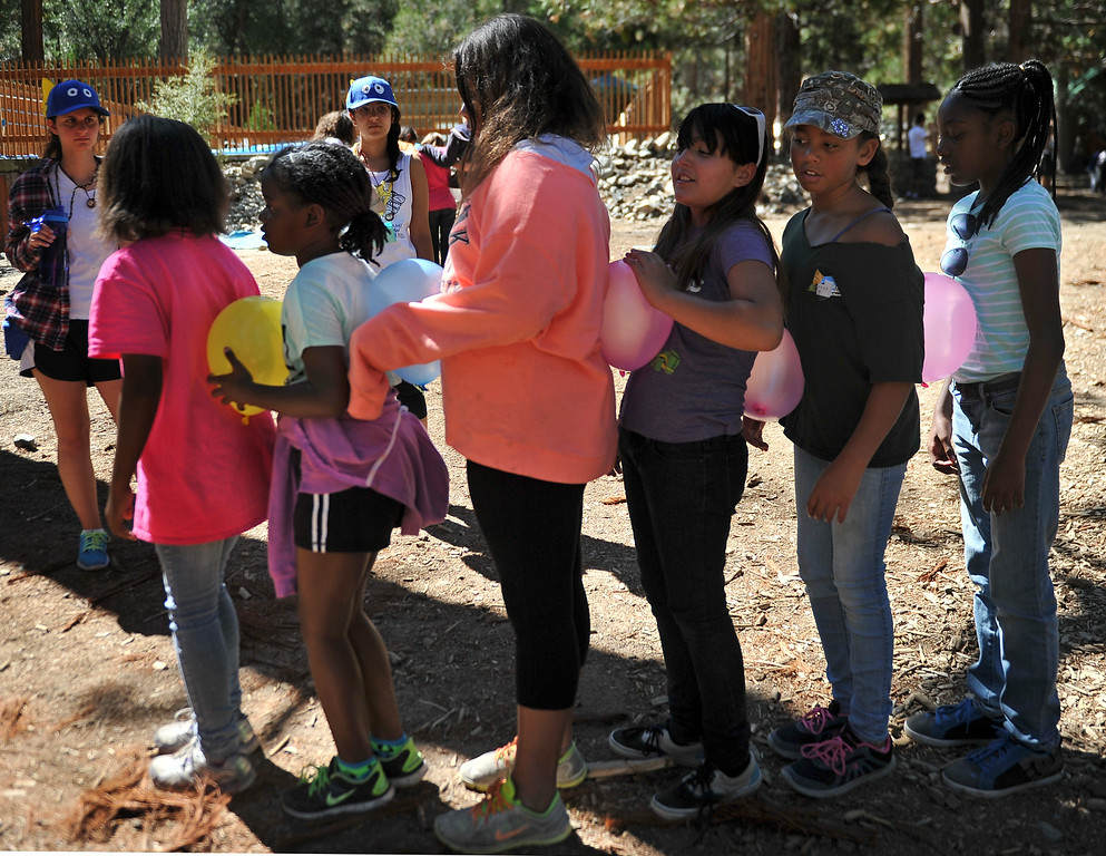". Young girls participate in an exercise titled, ""crossing the great divide,\"" that required them to get the entire team from start to finish while touching feet and later with a balloon between each person. The kids are enjoying the mountains for a week at Camp River Glen, a much different environment than their usual inner city home lives across Southern California. August 6, 2014. (Photo by Brittany Murray / Daily Breeze)"
