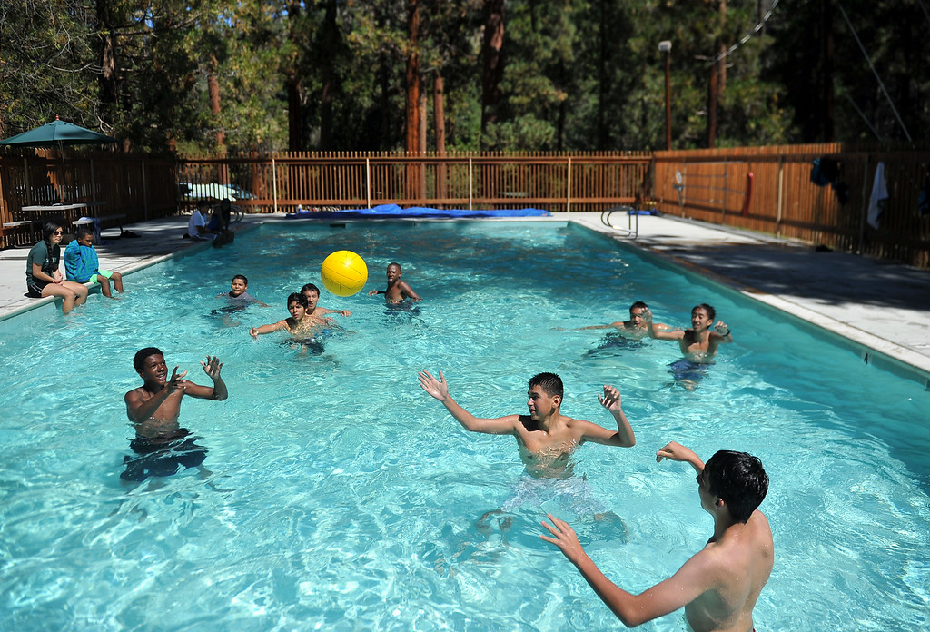 ". Young boys play a game of , ""freeze football,\"" in a pool surrounded by tall oak, cedar and pine trees. The kids are enjoying the mountains for a week at Camp River Glen, a much different environment than their usual inner city home lives across Southern California. August 6, 2014. (Photo by Brittany Murray / Daily Breeze)"
