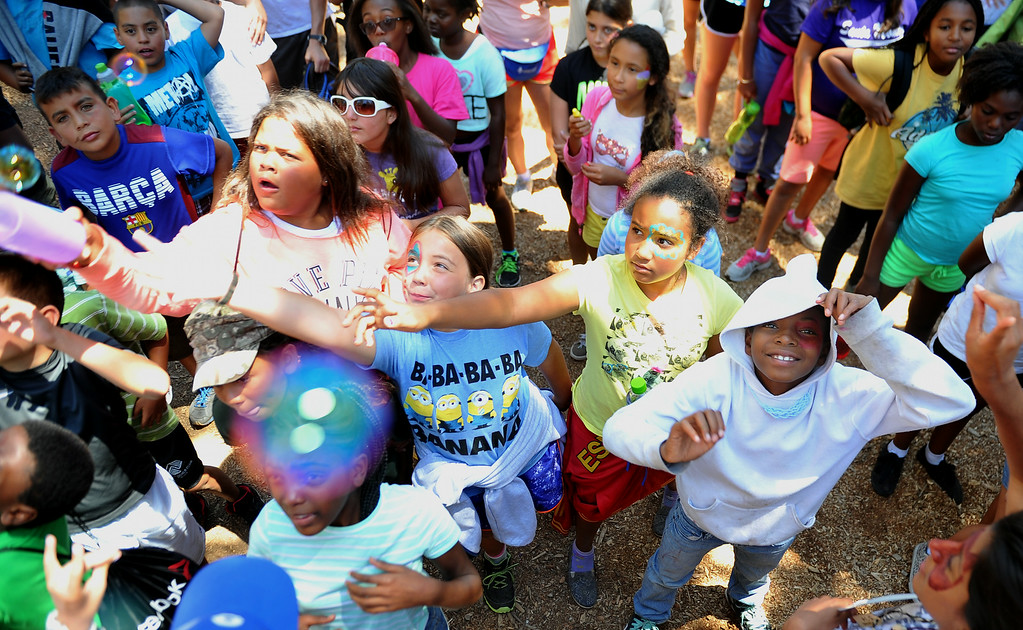. Some young Long Beach girls reach for bubbles while they wait for lunch. The kids are enjoying the mountains for a week at Camp River Glen, a much different environment than their usual inner city home lives across Southern California. August 6, 2014. (Photo by Brittany Murray / Daily Breeze)