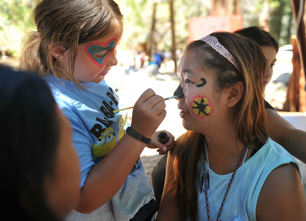 . Kourtney Gribble, 10, of Long Beach applies face paint to one of the counselors, Luna. The kids are enjoying the mountains for a week at Camp River Glen, a much different environment than their usual inner city home lives across Southern California. August 6, 2014. (Photo by Brittany Murray / Daily Breeze)