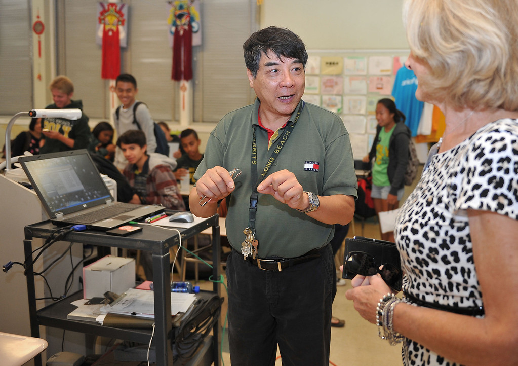 ". 10/16/13 - Dr. Zhu talks with Colleen Bentley at Poly High School on Wednesday morning, about the students language project to give directions from the school to a Long Beach landmark in Chinese. Bentley was participating in ""Principal for a Day,\"" an event that brings community members from the Greater Long Beach Area into schools in the role of the principal. It is co-sponsored by the Long Beach Area Chamber of Commerce, the Long Beach Unified School District and the Long Beach Education Foundation. (Photo by Brittany Murray/Press Telegram)"