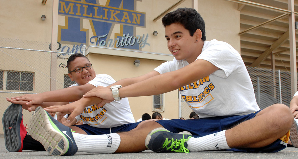 . L-R Adrian Barragan and Favien Ambriz stretch while students at Millikan High School participate in physical education in Long Beach. The 2013 Physical Fitness Test results for fifth-, seventh- and ninth-grade California students were released today, October 23, 2013. (Photo by Brittany Murray/Press Telegram)