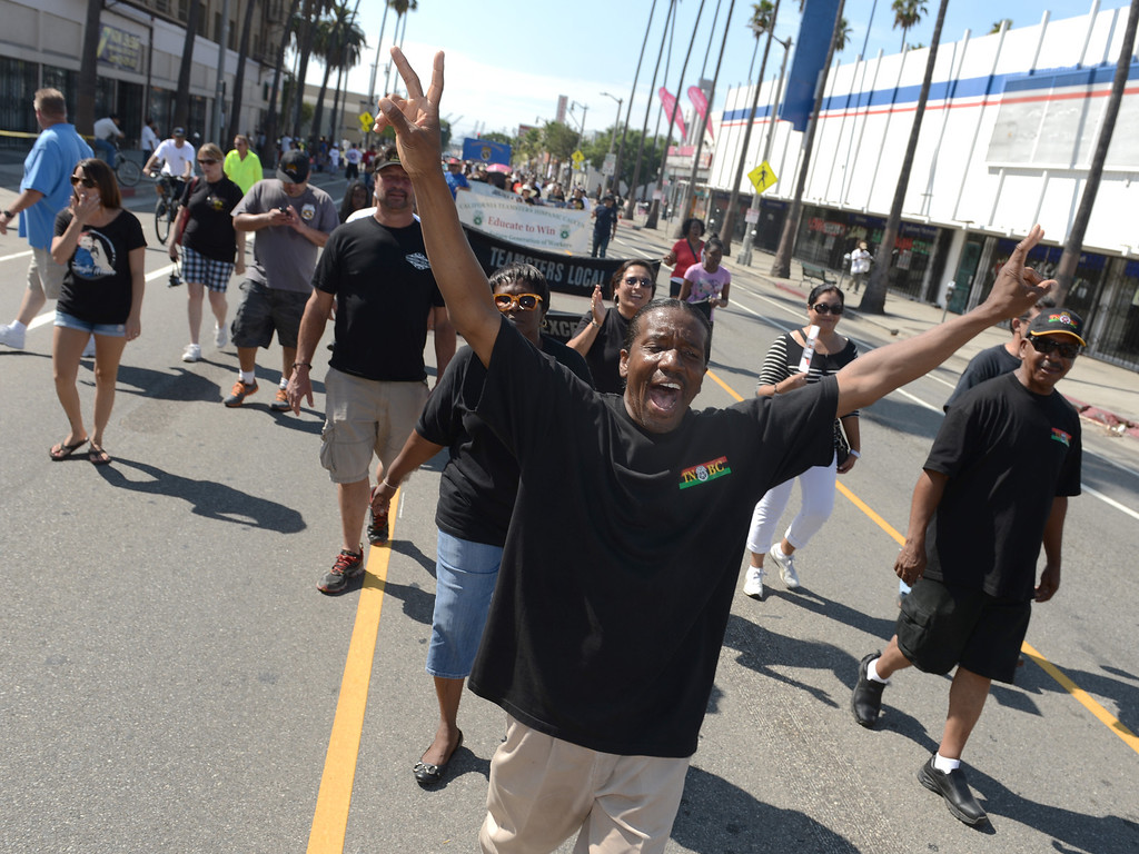 . Sylvester Anthony, of Pasadena, marches and cheers down Avalon Boulevard with the Teamsters as union workers and supporters from all over Southern California celebrate in the 34th annual Harbor Labor Day March and Rally in Wilmington September 2, 2013. (Thomas R. Cordova/Staff Photographer)