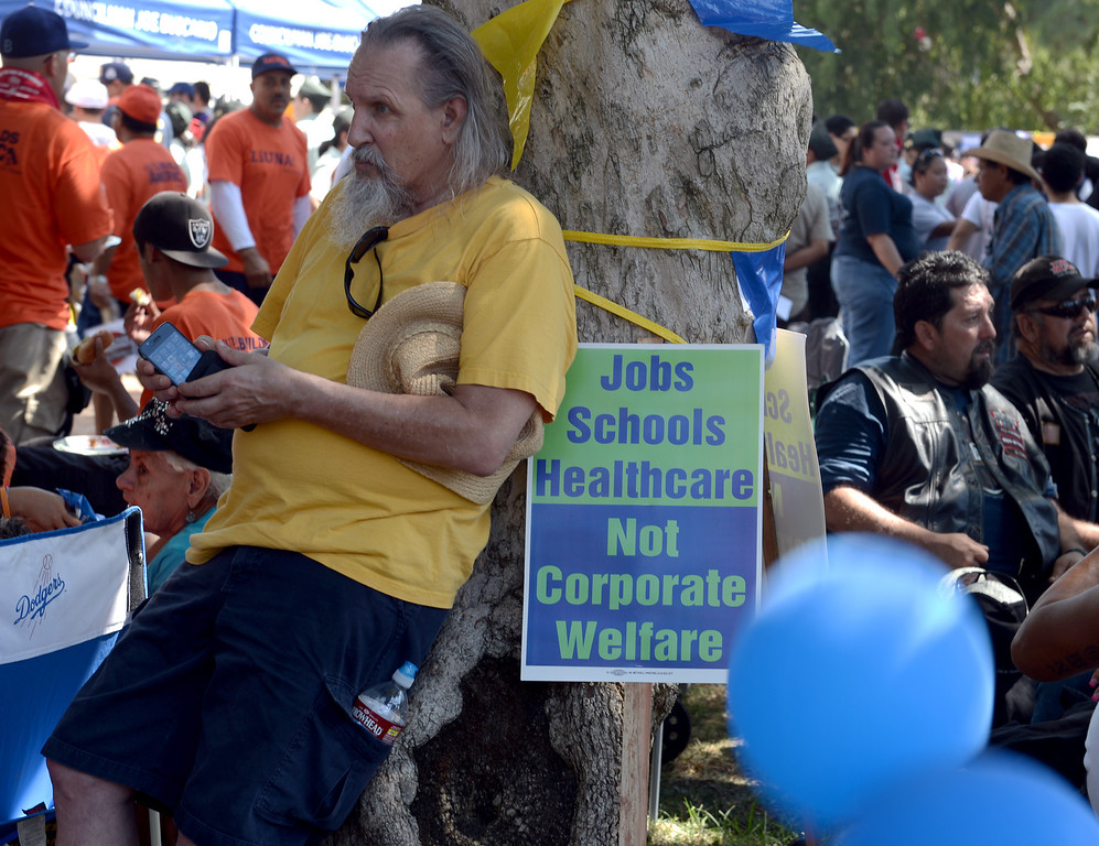 . Michael Lawrence, of Stanton, finds shade under a tree after the march as union workers and supporters from all over Southern California celebrate in the 34th annual Harbor Labor Day March and Rally in Wilmington September 2, 2013. (Thomas R. Cordova/Staff Photographer)