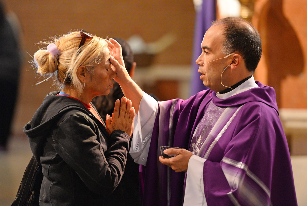 . Father Brian Nunez distributes ashes during Ash Wednesday Mass at Mary Star of the Sea Catholic Church in San Pedro.   (March 5, 2014. Photo by Brad Graverson/The Daily Breeze)