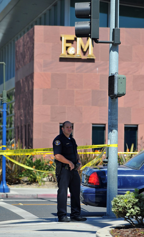 . The F&M Bank at 23rd and Bellflower was robbed around noon in Long Beach, CA on Tuesday, October 1, 2013 and the suspect got away with an undisclosed amount of cash.  An officer stands guard at the perimeter outside the F&M Bank. (Photo by Scott Varley, Daily Breeze)