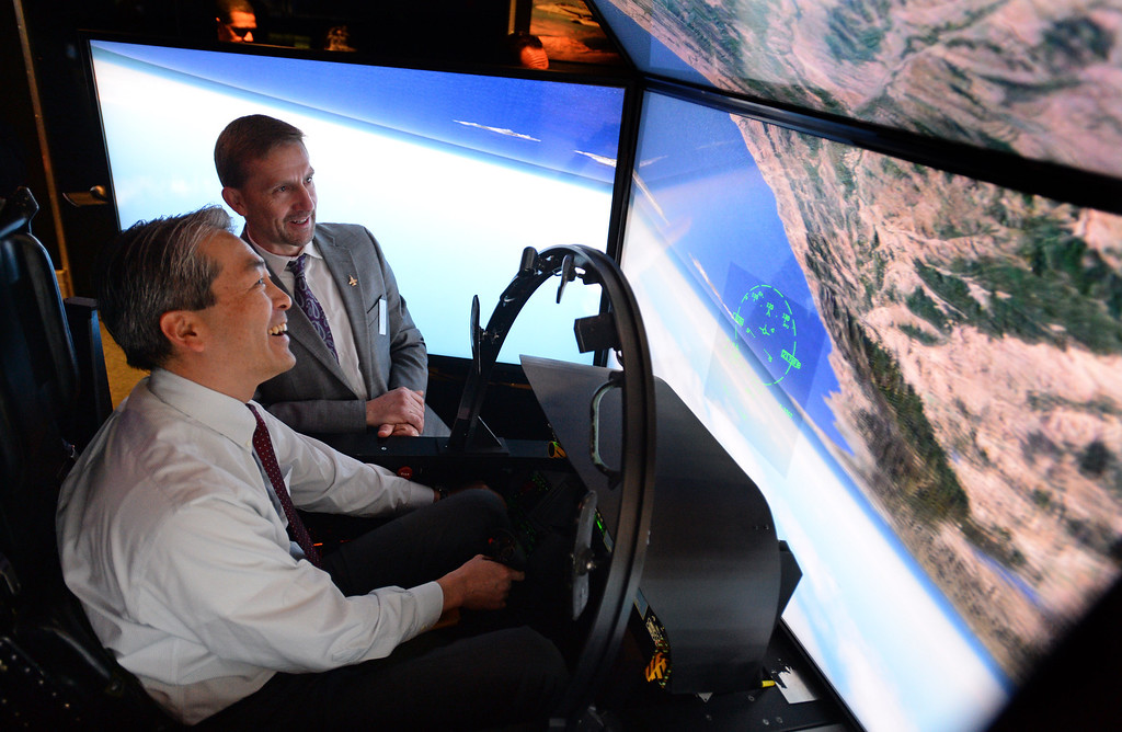 . Assemblyman Al Muratsuchi has his world turned upside down as he sits in a Boeing F/A-18 Super Hornet flight simulator while visiting Moog Aircraft Group in Torrance to attend a rally aimed at gathering support for building more advanced fighter jets. Boeing\'s John Keeven guides Muratsuchi through the controls. Photo by Brad Graverson 3-21-14