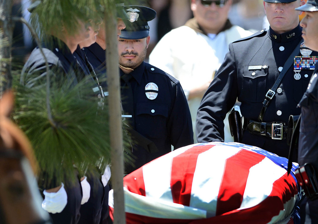 . LAPD officer Rich Medina,at left,  attends the burial service for his partner  LAPD Officer Roberto Sanchez, at The Good Shepherd Cemetery in Huntington Beach. Rich Medina was injured and his partner Roberto Sanchez was killed May 3 in a car crash in Harbor City. The Good Shepherd Cemetery in Huntington Beach.   Huntington Beach Calif., Wednesday, May 14,  2014.     (Photo by Stephen Carr / Daily Breeze)