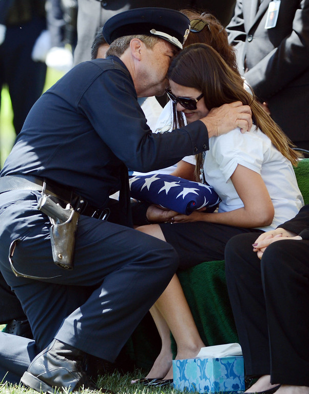 . LAPD Chief Charlie Beck gives Sonia Sanchez a kiss on the forehead after he handed her the American flag that was draped on her husband LAPD Officer Roberto Sanchez\'s coffin, during burial services at The Good Shepherd Cemetery in Huntington Beach.  Officer Sanchez was killed May 3 in a car crash in Harbor City. The Good Shepherd Cemetery in Huntington Beach.   Huntington Beach Calif., Wednesday, May 14,  2014.     (Photo by Stephen Carr / Daily Breeze)