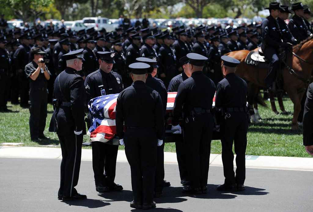 . LAPD officers carry the flag draped coffin of LAPD Officer Roberto Sanchez,during burial services at The Good Shepherd Cemetery in Huntington Beach. Sanchez was killed May 3 in a car crash in Harbor City. The Good Shepherd Cemetery in Huntington Beach.   Huntington Beach Calif., Wednesday, May 14,  2014.     (Photo by Stephen Carr / Daily Breeze)