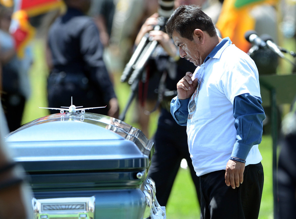 . Francisco Sanchez, father of LAPD Officer Roberto Sanchez, takes a moment after placed a model airplane on his sons coffin during burial services at The Good Shepherd Cemetery in Huntington Beach. His son Officer Roberto Sanchez, who loved to build model airplanes,  was killed May 3 in a car crash in Harbor City. The Good Shepherd Cemetery in Huntington Beach.   Huntington Beach Calif., Wednesday, May 14,  2014.     (Photo by Stephen Carr / Daily Breeze)