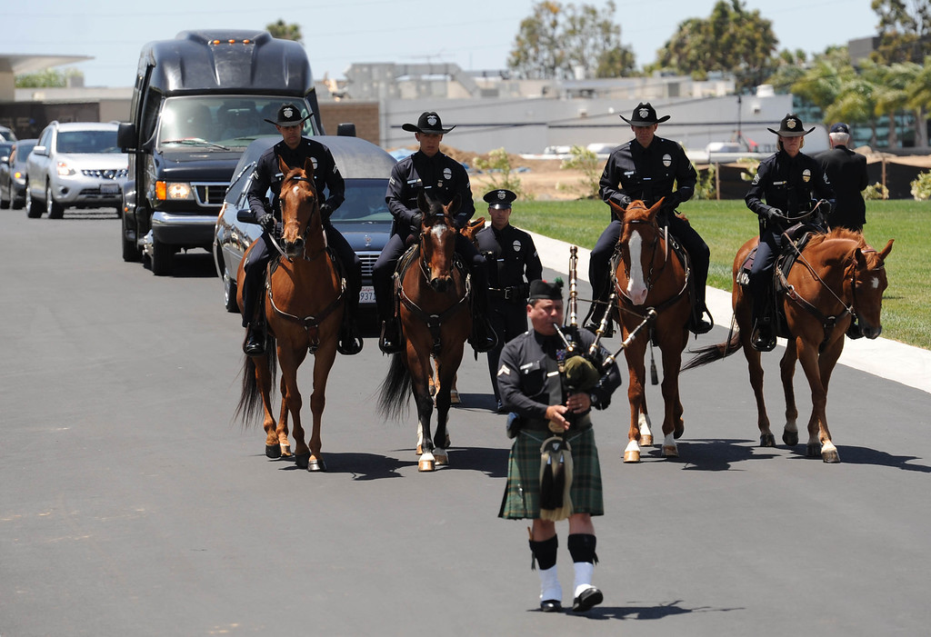 . A riderless LAPD horse leads the hearse containing LAPD Officer Roberto Sanchez, during burial services for Sanchez,  held at The Good Shepherd Cemetery in Huntington Beach. Sanchez was killed May 3 in a car crash in Harbor City. The Good Shepherd Cemetery in Huntington Beach.   Huntington Beach Calif., Wednesday, May 14,  2014.     (Photo by Stephen Carr / Daily Breeze)