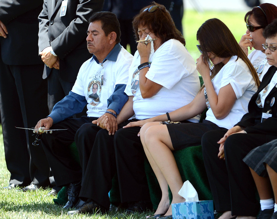 . During burial services for LAPD Officer Roberto Sanchez, from left to right, father and mother Francisco Sanchez and Patricia Sanchez and wife Sonia Sanchez emotional at his graveside at The Good Shepherd Cemetery in Huntington Beach. Officer Sanchez was killed May 3 in a car crash in Harbor City. The Good Shepherd Cemetery in Huntington Beach.   Huntington Beach Calif., Wednesday, May 14,  2014.     (Photo by Stephen Carr / Daily Breeze)