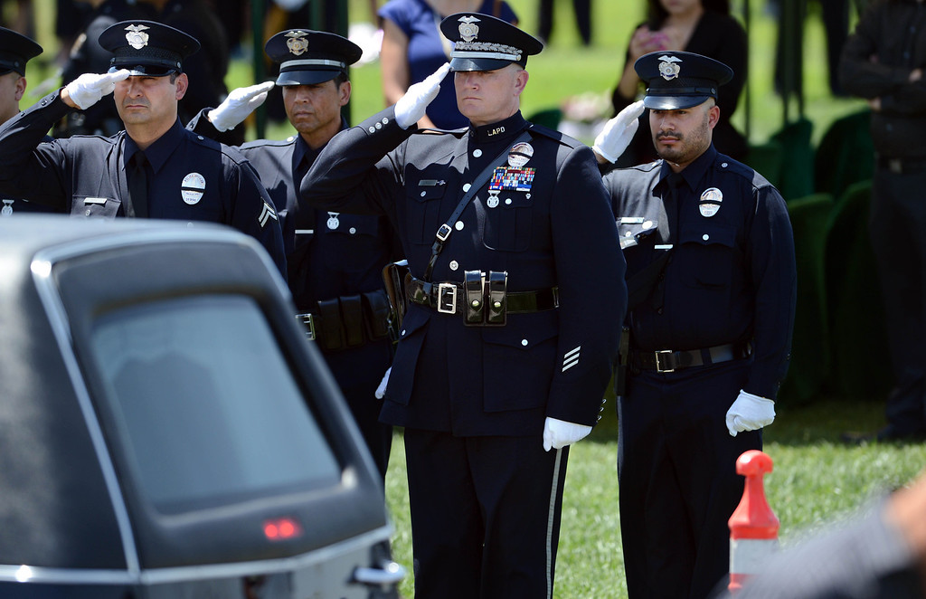 . LAPD officer Rich Medina, right, attends the burial service for his partner  LAPD Officer Roberto Sanchez, at The Good Shepherd Cemetery in Huntington Beach. Rich Medina was injured and his partner Roberto Sanchez was killed May 3 in a car crash in Harbor City. The Good Shepherd Cemetery in Huntington Beach.   Huntington Beach Calif., Wednesday, May 14,  2014.     (Photo by Stephen Carr / Daily Breeze)
