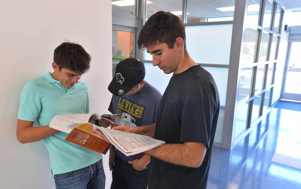 . Three students leaf through the schedule of classes. (sorry no ids) First day of classes at Cerritos College for the fall semester. Students will see new buildings, programs and food services. Enrollment is up 5.8%. (Aug. 18 2014 Photo by Brad Graverson/The Press Telegram)