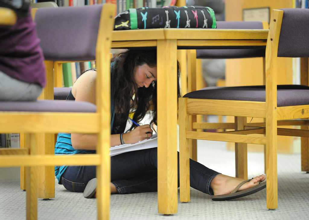 . At El Camino College, a student in the library continues to study as she takes cover under a desk during the Great California Shake Out, held Thursday morning throughout the state. Photo by Brad Graverson/The Daily Breeze 10/17/13