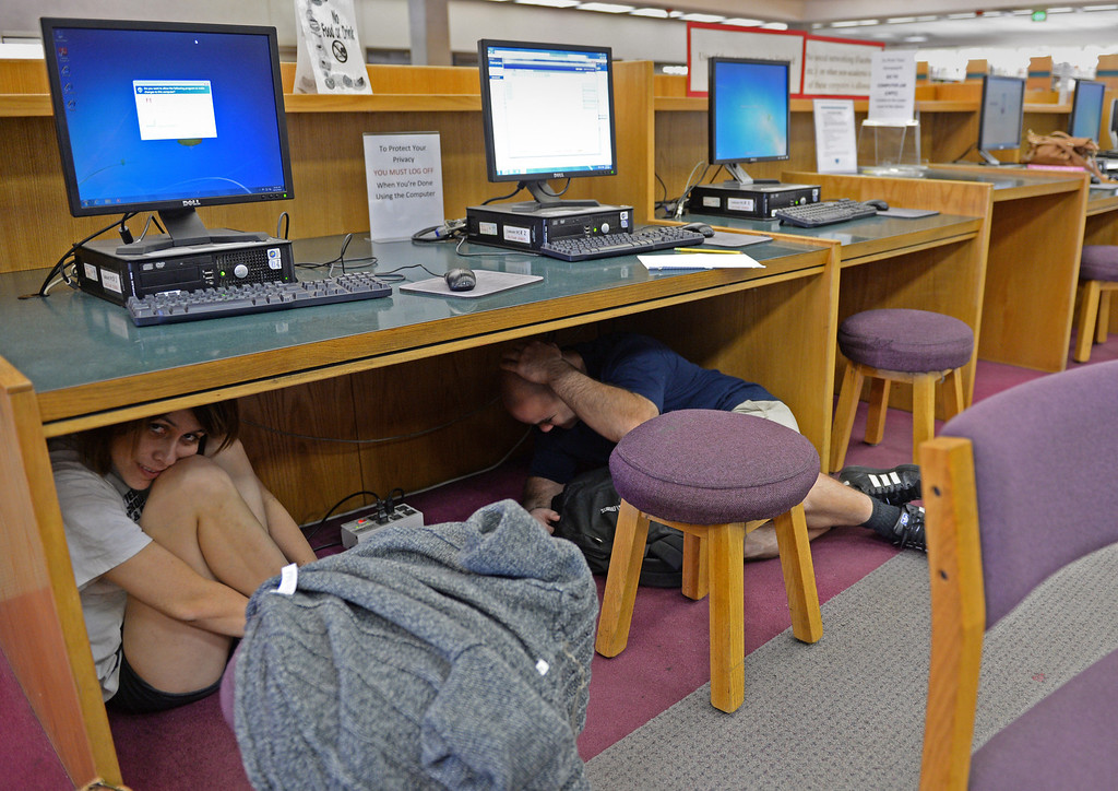 . At El Camino College,  students in the library take cover under a desk during the Great California Shake Out, held Thursday morning throughout the state. Photo by Brad Graverson/The Daily Breeze 10/17/13