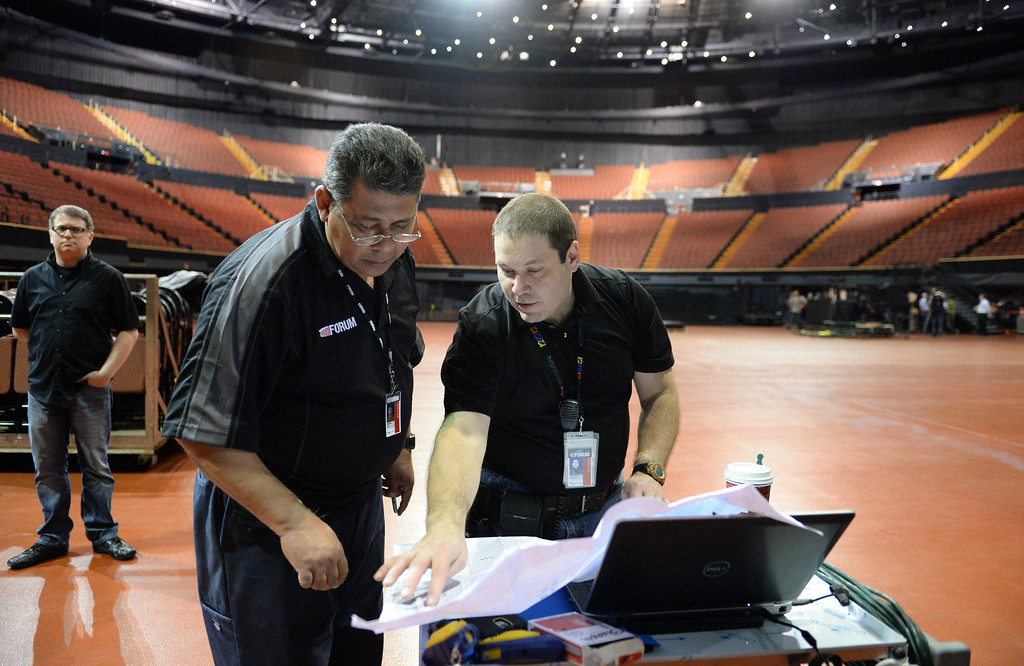 ". The new entertainment venue, the ""Fabulous\"" Forum in Inglewood has undergone a $100 million renovation, and is set to host the Eagles concert series starting Jan 15.  VP of Event Production Timothy Parsaca, center, goes over details with Jim Barto, left, as production ramps up for the Eagles 6-night concert run.   (Jan 14, 2014. Photo by Brad Graverson/The Daily Breeze)"