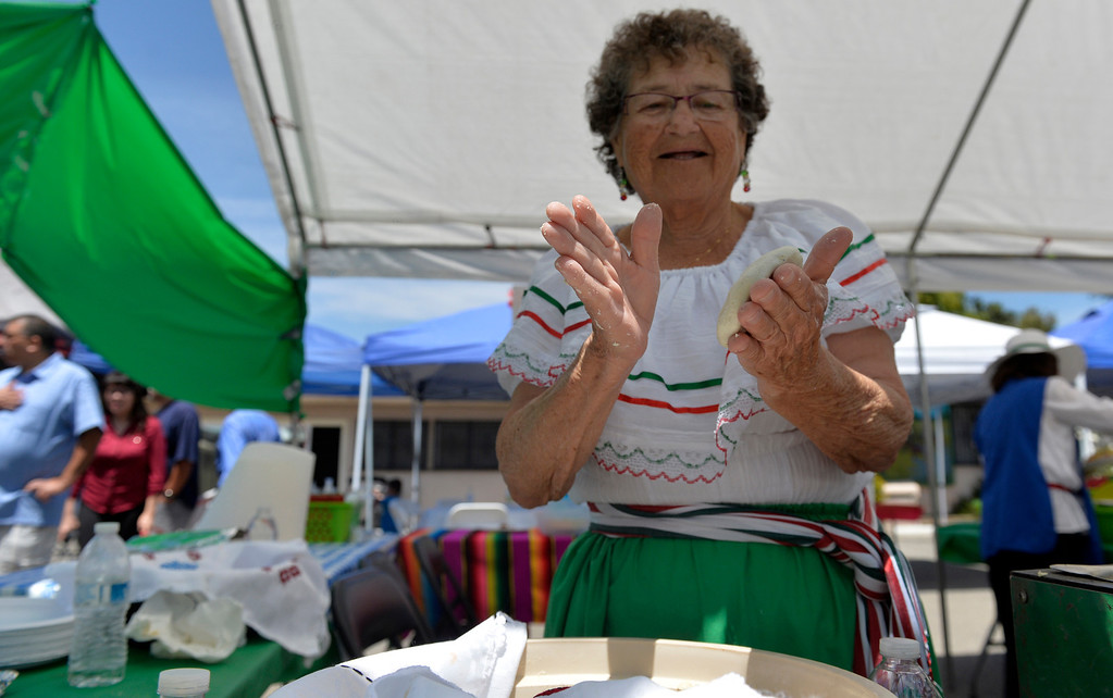 . Irene Gomez pats out masa as she makes gorditas at a Cinco de Mayo Fiesta at St. Isidore Historical Plaza in Los Alamitos, CA. Sunday May 4, 2014.The celebration had folklorico dancers, a choir and a Mariachi band. In 1926, this historic landmark was built. It was named St. Isidore after the patron Saint of laborers and farm workers. St. Isidore was celebrating more than Cinco de Mayo, as of last week it pasted escrow so all the money raised during the event go\'s to preserving the plaza. The once Catholic church is now non-denominational church. (Thomas R. Cordova-Daily Breeze/Press-Telegram)