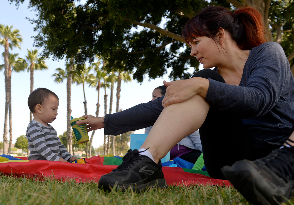 . Yve Hart hands her son RaYa, 1, a sippy cup as a group of mothers and their children gather at Marine Stadium in Long Beach, CA. Monday April 21, 2014. (Thomas R. Cordova-Daily Breeze/Press-Telegram)