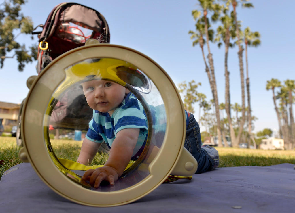 . Harrison Hinkel, 1, is seen through a toy drum as a group of mothers and their children gather at Marine Stadium in Long Beach, CA. Monday April 21, 2014. The mothers gather every morning at different locations throughout city.  (Thomas R. Cordova-Daily Breeze/Press-Telegram)