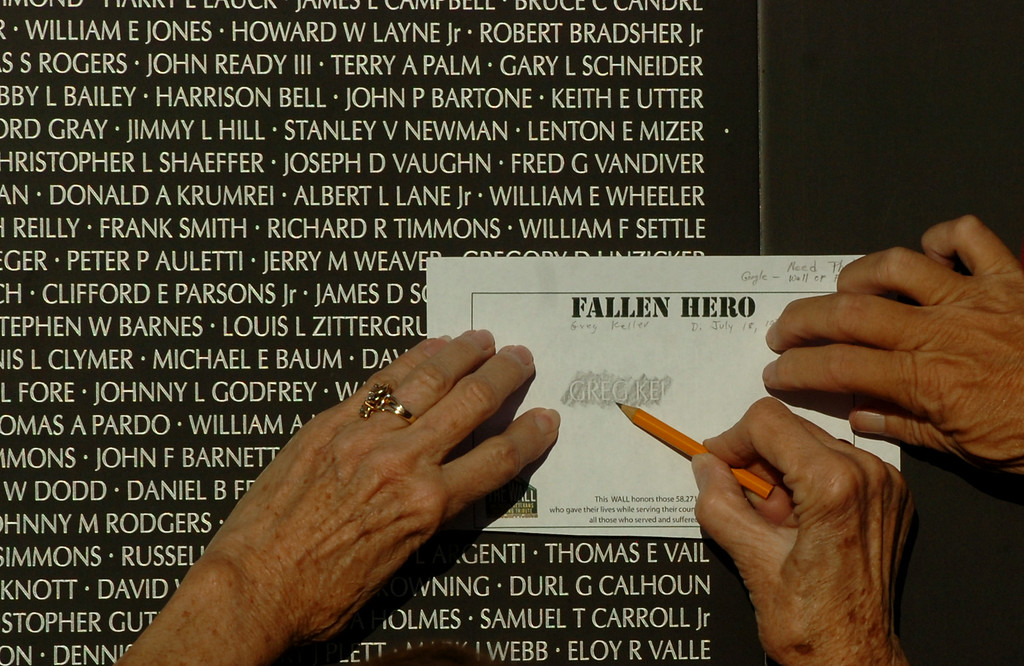. Ricky Campbell rubs out her cousins name off the traveling Vietnam Veterans Memorial Wall which is on display at Lakewood\'s Mayfair Park in Lakewood CA. Thursday August 14, 2014. The traveling wall is 80 percent-sized replica is 360-feet long. (Thomas R. Cordova-Daily Breeze/Press-Telegram)