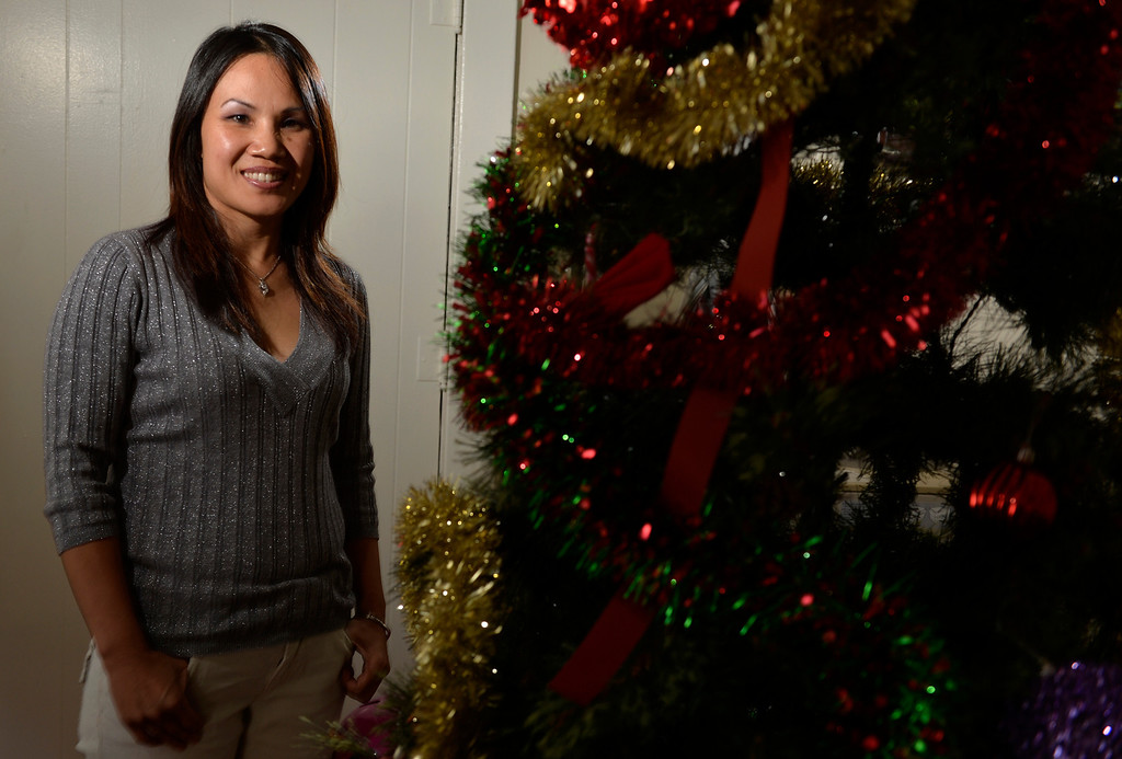 ". Lakhena ""Lucky\"" Chhuon stands stands next to a Christmas tree at a home in Long Beach, CA. Friday December 20, 2013. Chhuon, Project Coordinator,  who conducts relief efforts around the world through the nonprofit Rescue Task Force, which responds to man-made and natural disasters. (Thomas R. Cordova/Press-Telegram/Daily Breeze)"