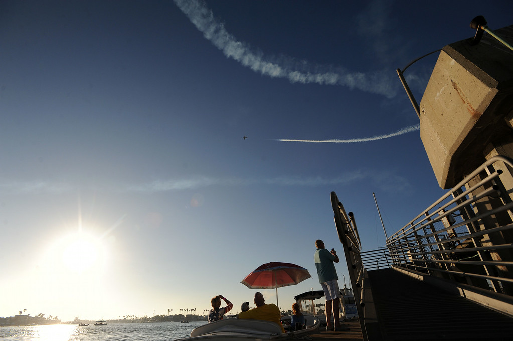 . Party goers look on as vintage aircraft flyover during the Big Bang on the Bay,  a community  block party that took place from 5:30 to 9:30 p.m. at The Boathouse on the Bay.  The party featured live music food,  parachutists and topped off by Fireworks over Alamitos Bay. Long Beach Calif.,  Thursday July 3,  2014.    (Photo by Stephen Carr / Daily Breeze)