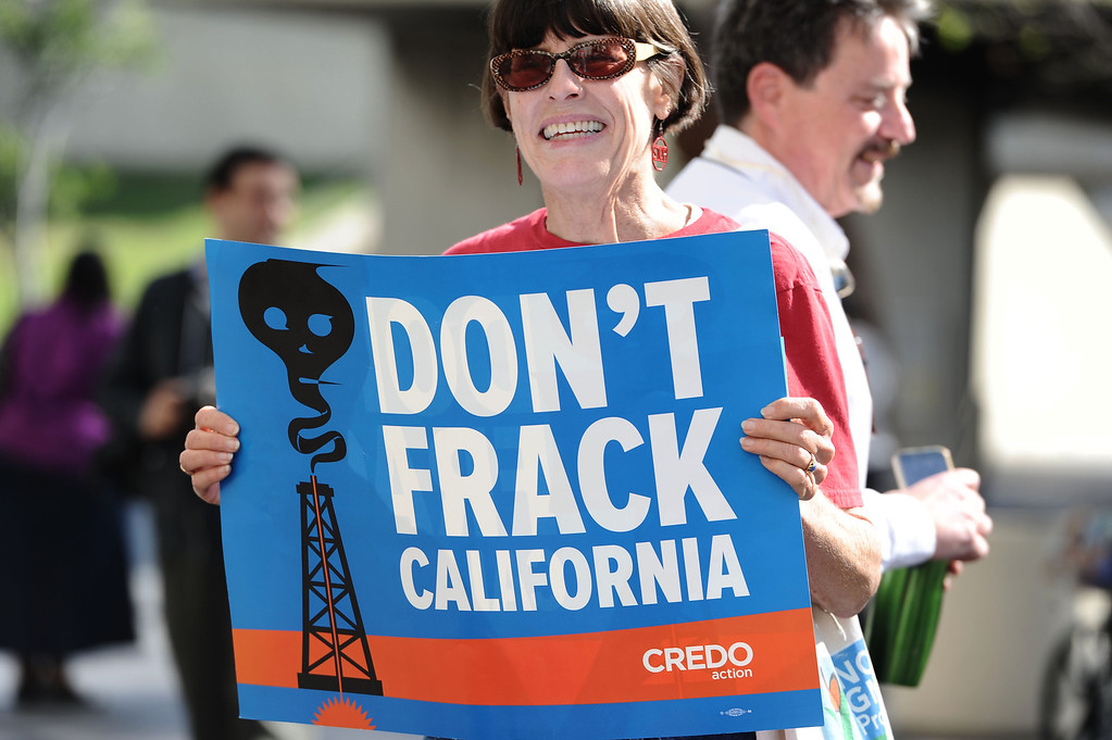 """. Environmentalists wearing hazmat suits and carrying boogie boards protest \""""fracking\"""" outside the Coastal Commission\'s meeting at Long Beach City Hall in Long Beach, CA. on Wednesday March 12, 2014. (Photo by Sean Hiller/ Daily Breeze)."""