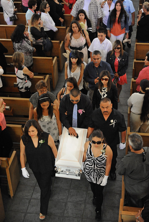 . Rudy Coronado, center, caresses the smallest casket as it is taken from the church by family members. Funeral services for three murdered Coronado children from the Carson area at St. Anthony of Padua Church in Gardena.   (June 2, 2014 Photo by Brad Graverson/The Daily Breeze)
